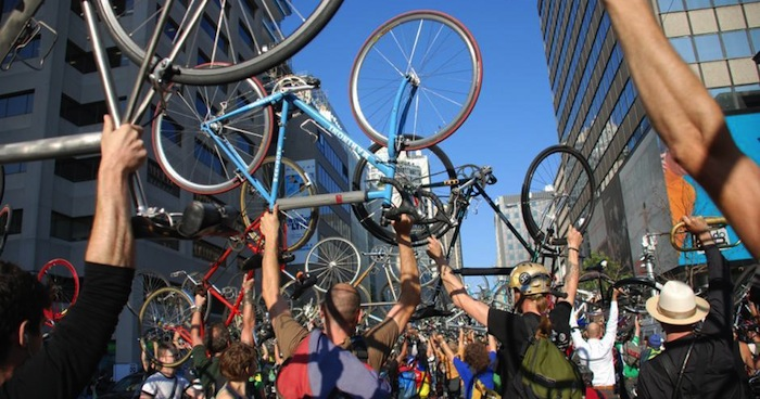 Community of cyclists with road bikes rasied in the air