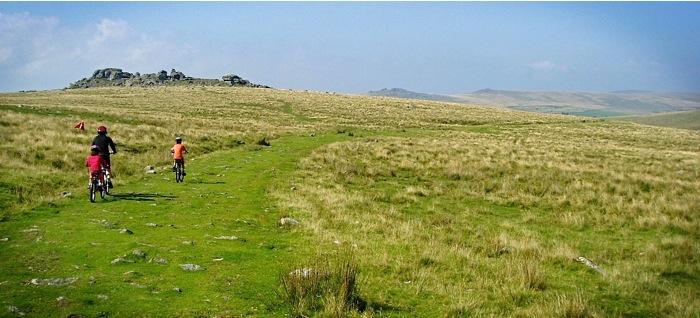 Family cycling on grassy hilltop Dartmoor