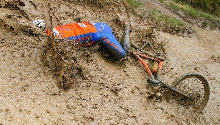 mountain bike rider crashes full-body into mud bath