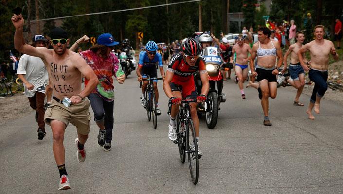 fans running aside cyclists up a climb