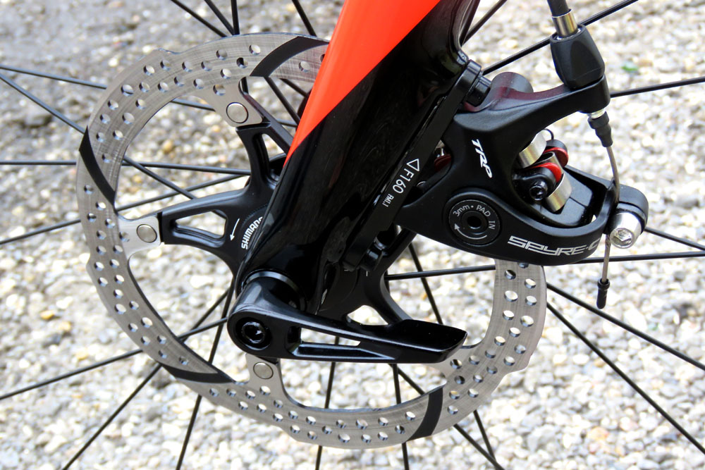Close up of the front disc brake caliper, rotor, and thru-axle of the Specialized Roubaix Elite Disc