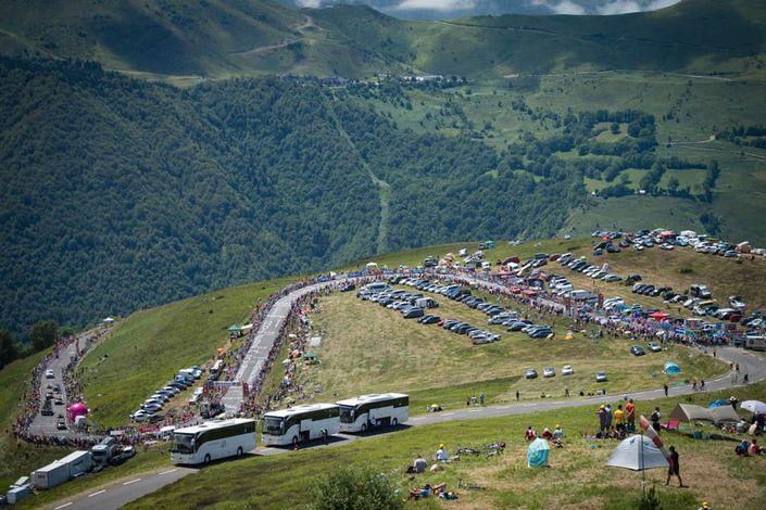 Race vehicles, caravan, and fans amass on a Tour de France climb.