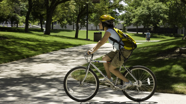 Student on bicycle with helmet and backpack