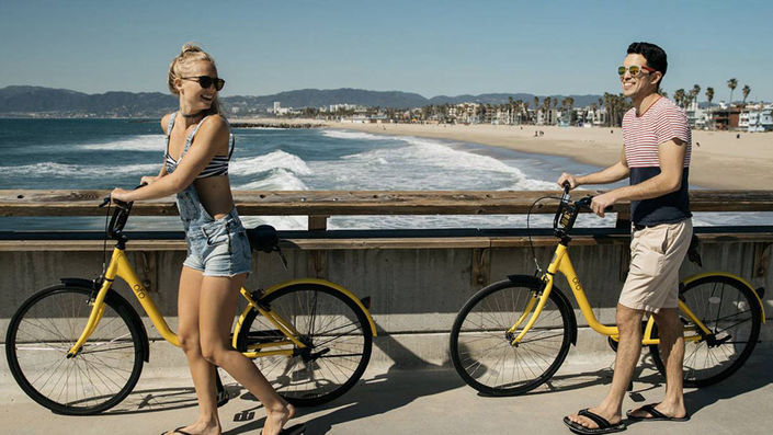 Young adults enjoying bike share bicycles from Ofo