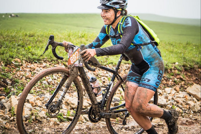 Muddy, happy women's rider at Dirty Kanza
