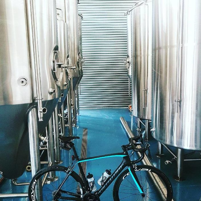 Head Brewer of Helios Brewing, Charlie Hodgson, parks his Tarmac Pro Race amongst the brewery tanks. image: Helios Brewing